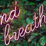 Cartel luminoso con texto que dice And breathe